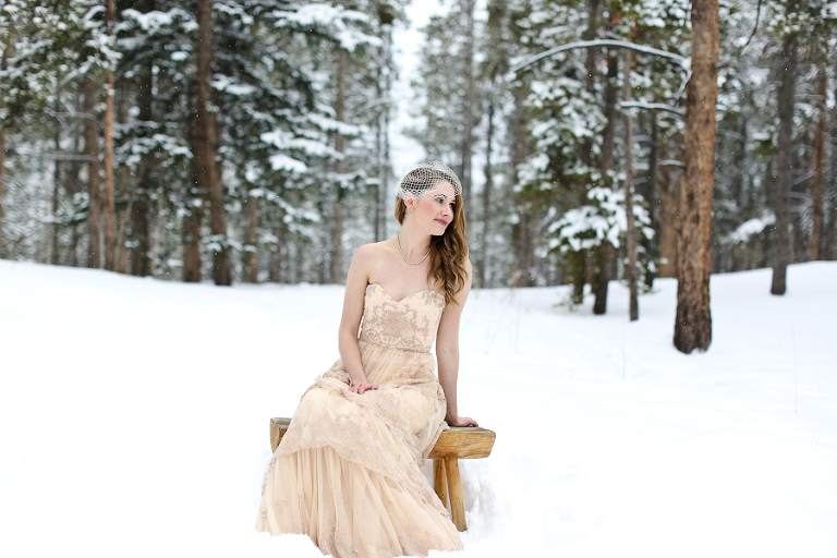 bride eloping in a snowy forest in colorado sitting on a wood bench