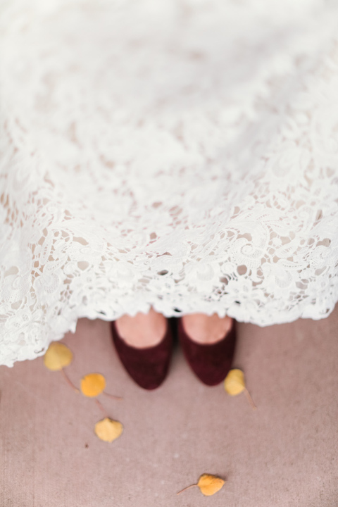 lace wedding dress with burgundy shoes in the fall with aspen leaves