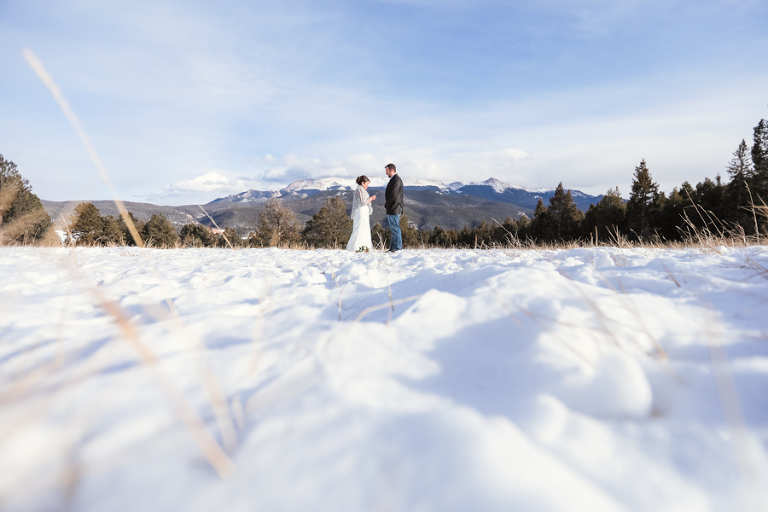 bride and groom self-solemnize their own vows in colorado during a winter elopement