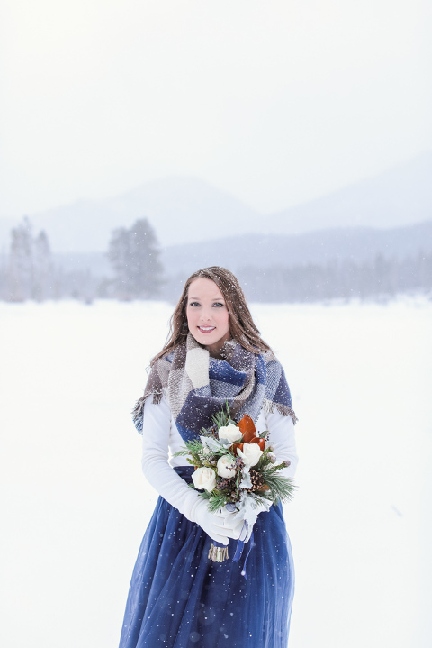 A bride stands in the snow after her elopement ceremony at Sprague Lake in December inside RMNP. Photographed by Becky Young Photography