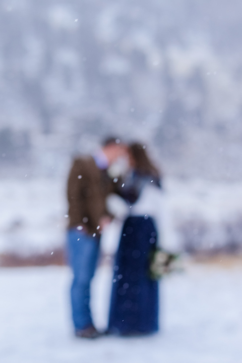 softly falling snow surrounds a bride and groom who eloped in the winter inside Rocky Mountain National Park