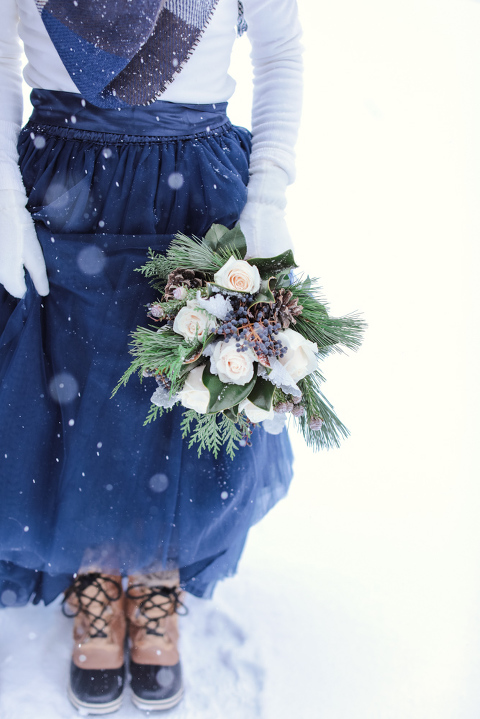 Winter elopement attire of sorel boots and a blanket scarf with a blue tule skirt in the snowy mountains of Colorado with a pinecone bouquet