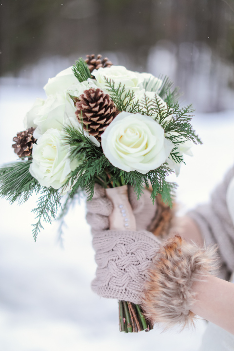 fur trimmed gloves of the bride hold her winter elopement bouquet with pinecones and pine needles