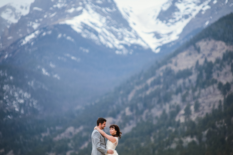 A couple elopes in RMNP with the mountains behind them