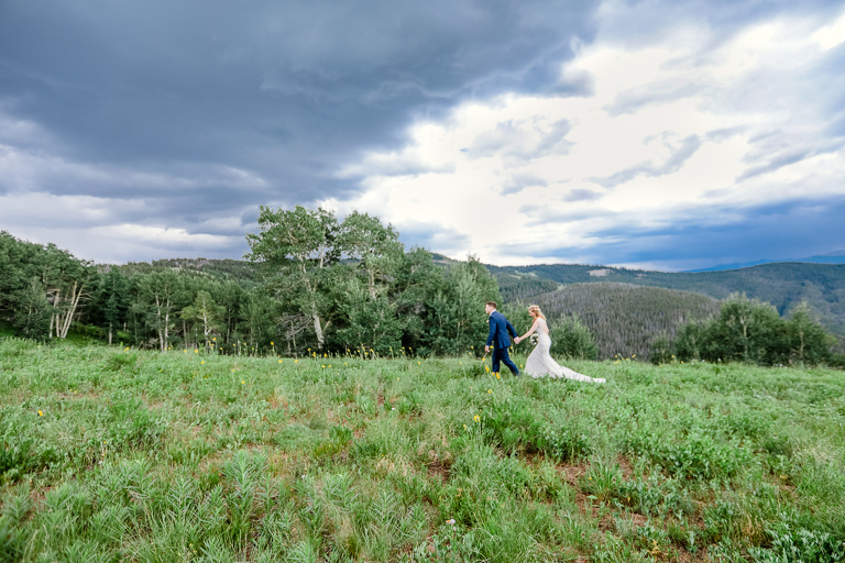 A bride and groom walk to their ceremony site as they elope in Vail
